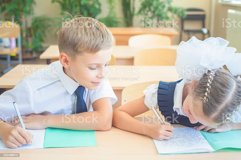 Students or classmates in school classroom sitting together at desk stock photo