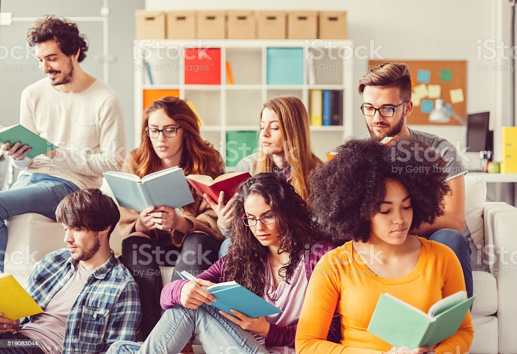Students reading books in the campus library stock photo