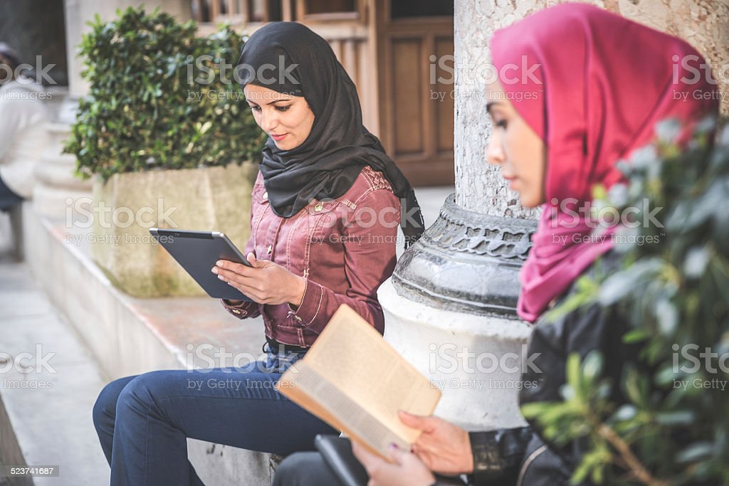 Students Reading On Paper Book And Tablet stock photo