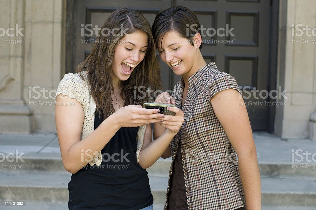 Students Reading Text Message on Modile Phone royalty-free stock photo