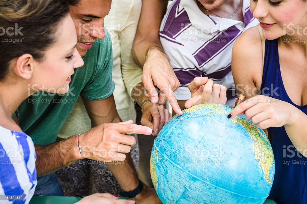students searching place on a globe stock photo