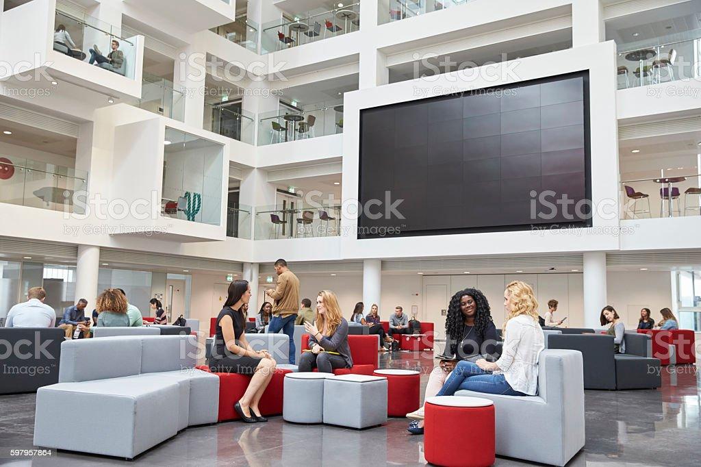Students sit talking under AV screen in atrium at university stock photo