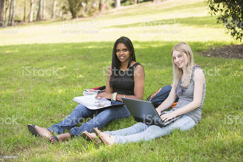 Students Sitting on the Grass Studying stock photo