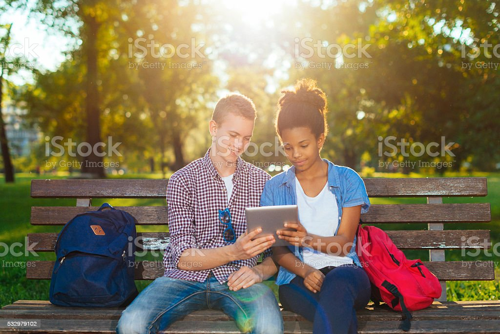 Students spending time in park with digital tablet stock photo