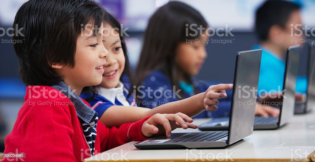 Students Using a Laptop Together stock photo