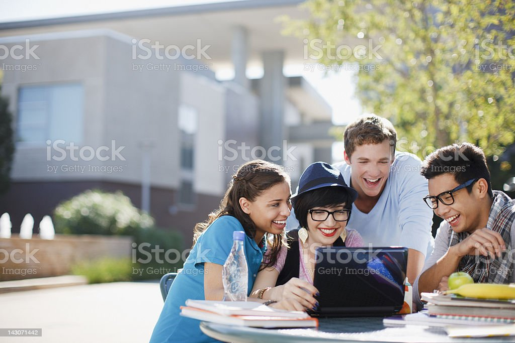 Students using laptop together outdoors stock photo