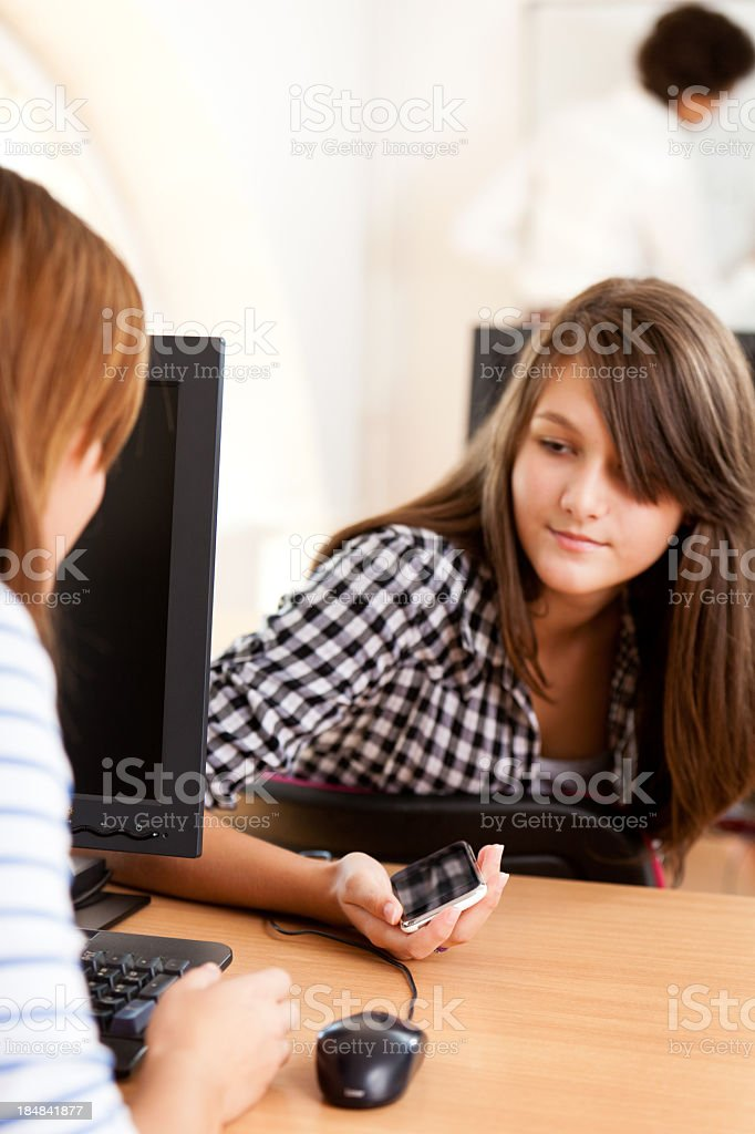 Students using mobile phone in the classroom royalty-free stock photo