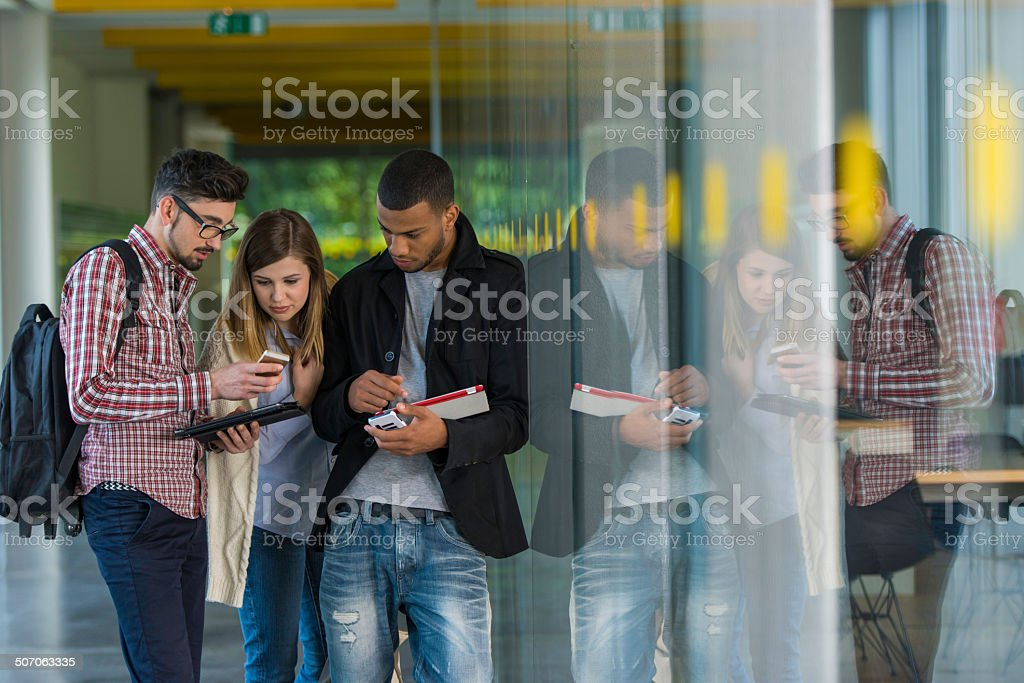 Students Using Mobile Phones In The Corridor stock photo