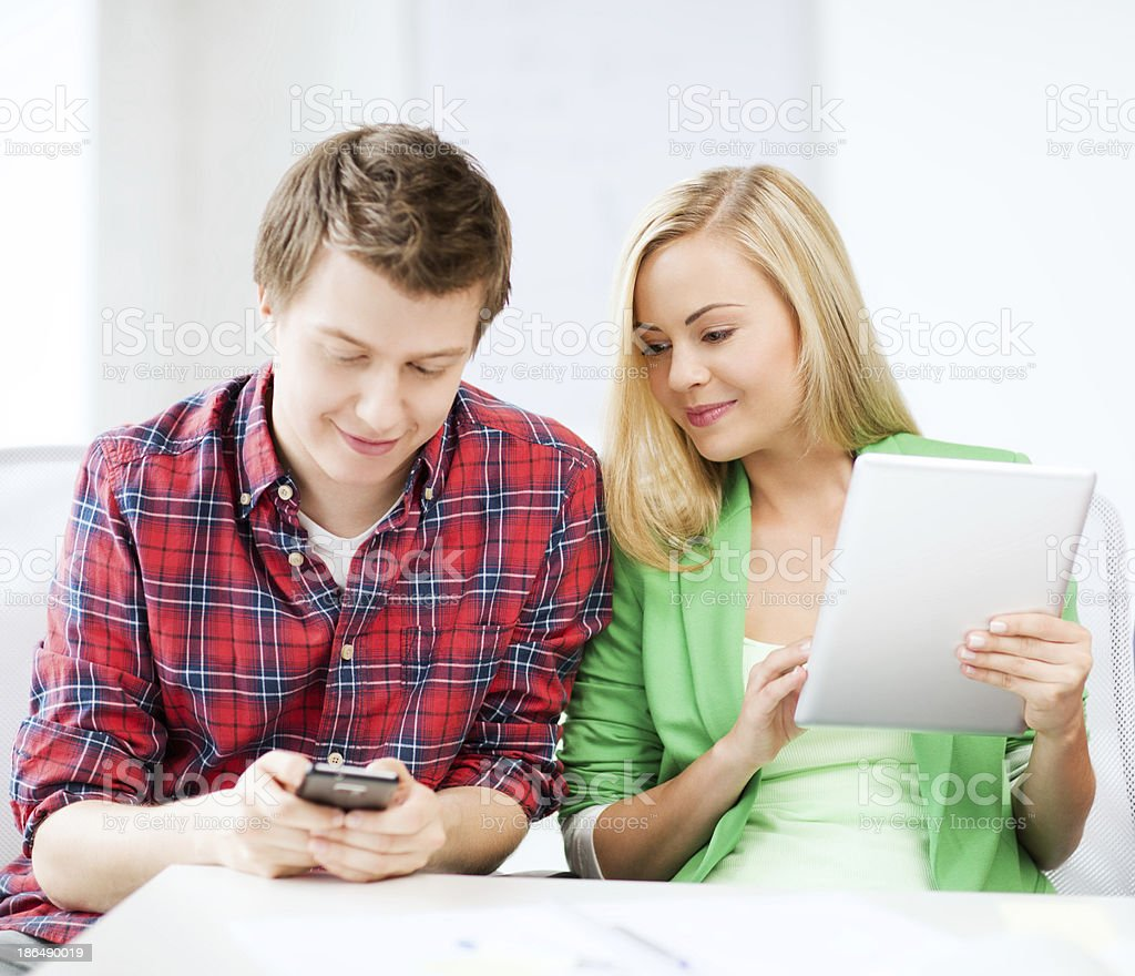students using smartphone and tablet pc at school royalty-free stock photo