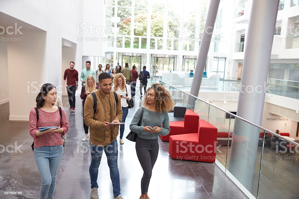 Students walk and talk using mobile devices in university stock photo