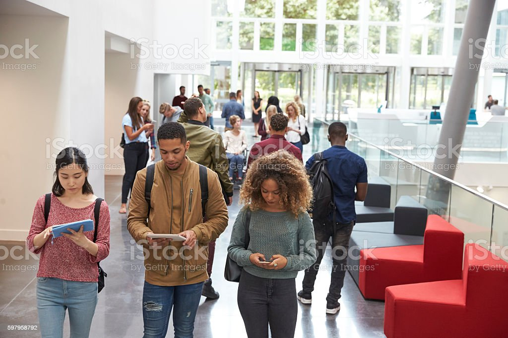 Students walk in university campus using tablets and phone stock photo