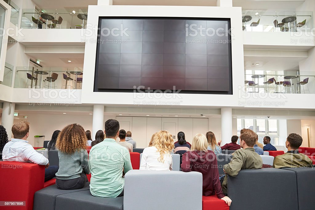 Students watching big screen in university atrium, back view stock photo