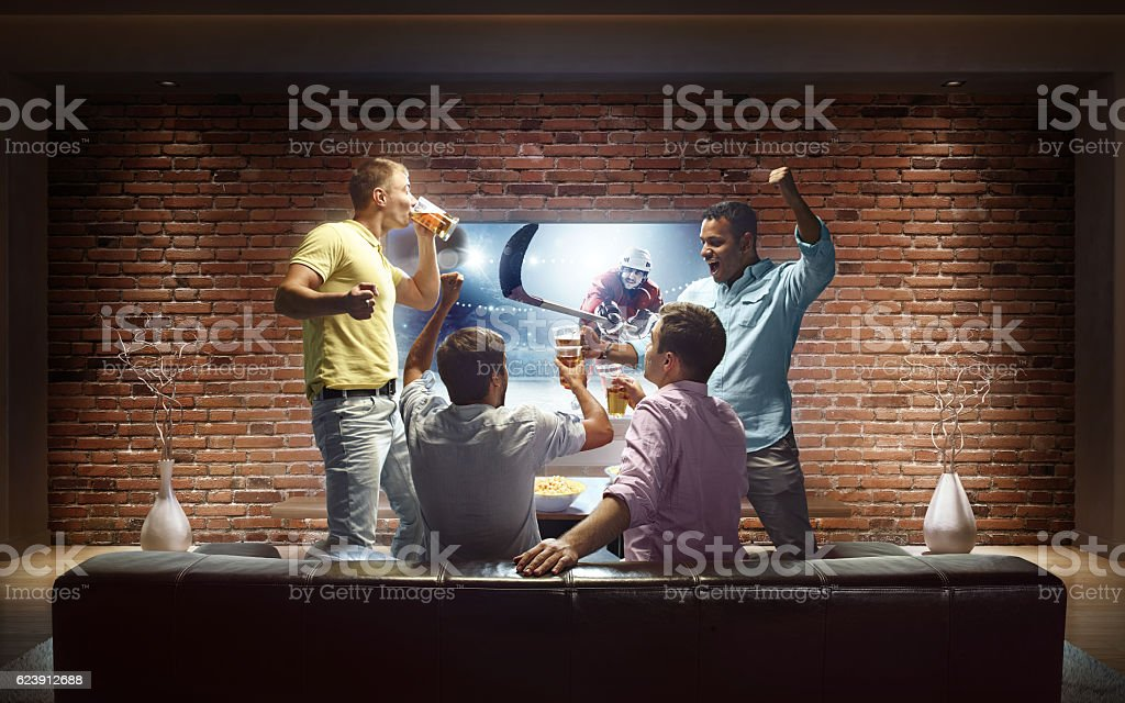 A group of young male friends are cheering while watching Ice Hockey...