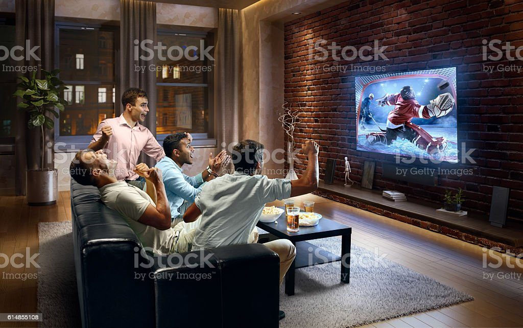 A group of young male friends cheering while watching Ice Hockey game...