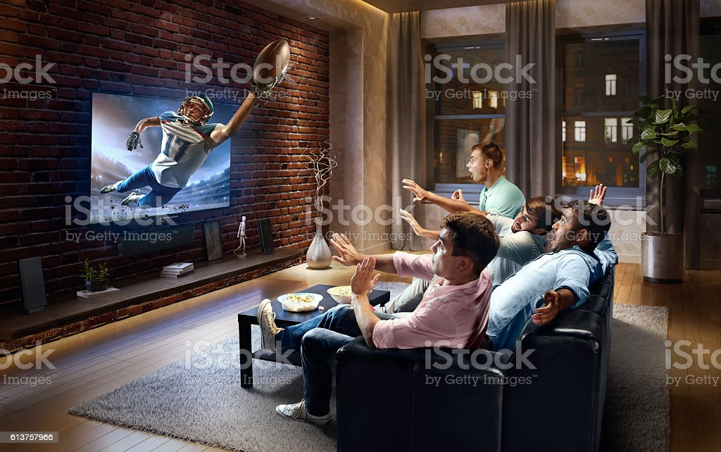 Students watching very realistic American football game on TV stock photo