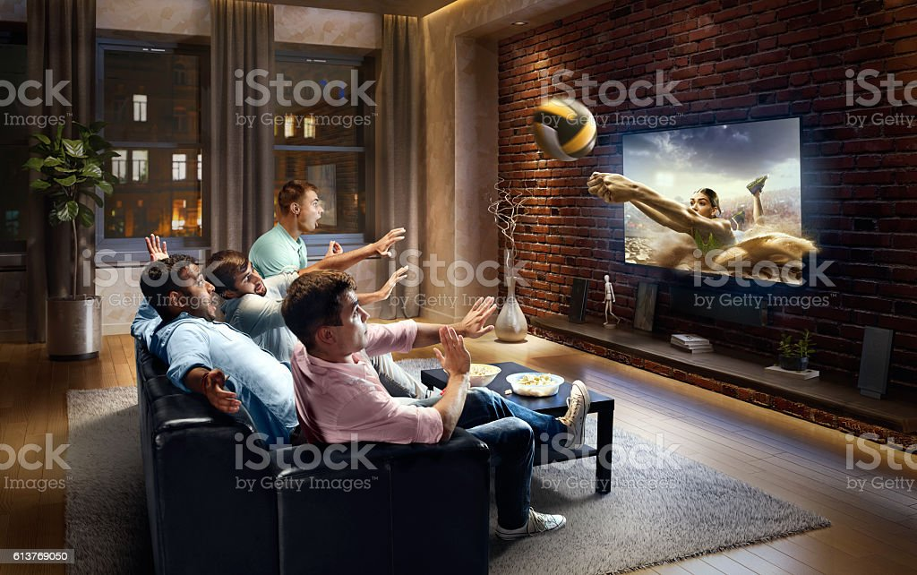 Students watching very realistic Volleyball game on TV stock photo