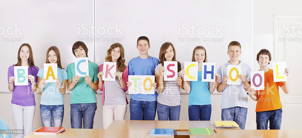 Students with  BACK TO SCHOOL message on placards. royalty-free stock photo