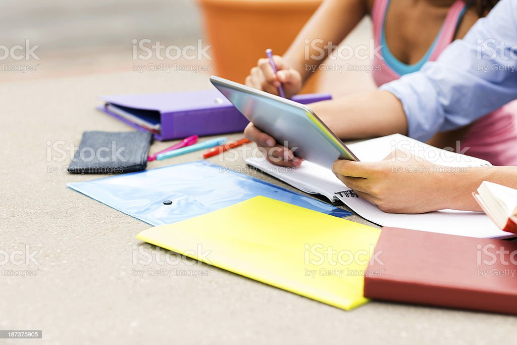 Students With Books And Digital Tablet Sitting At Table royalty-free stock photo