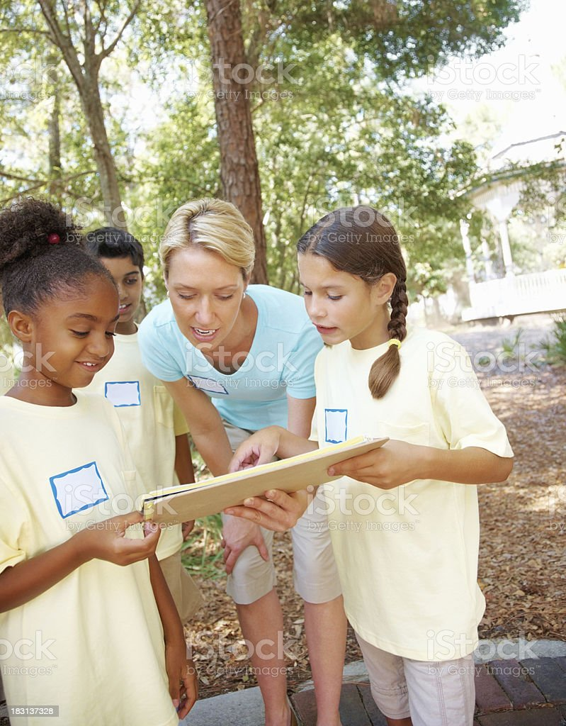 Students with teacher discussing something from sketch book royalty-free stock photo