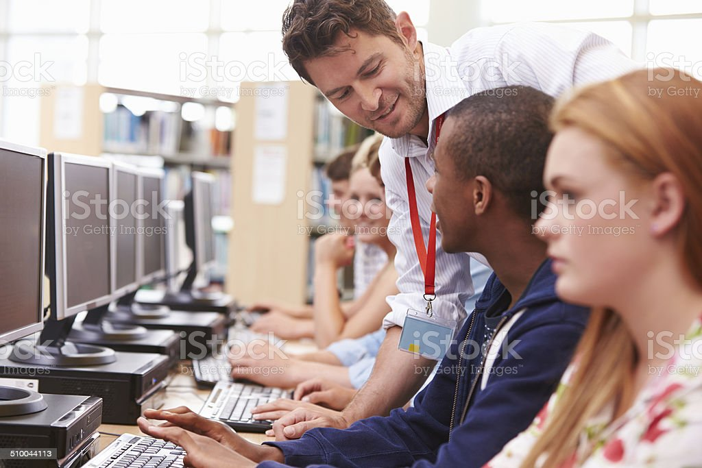 Students Working At Computers In Library With Teacher stock photo
