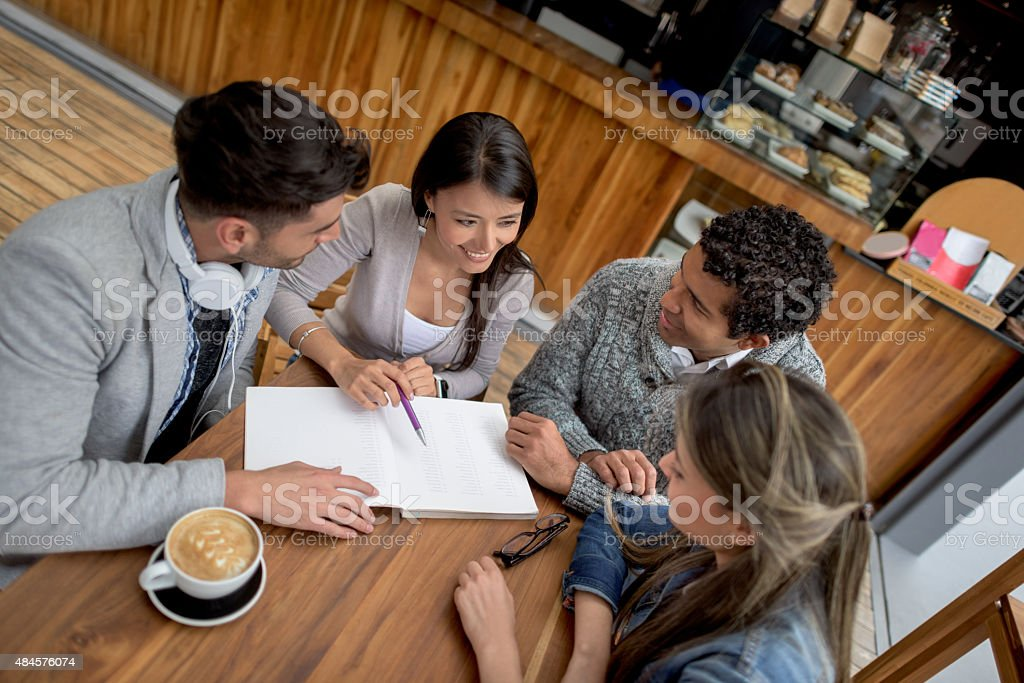 Students working together at a coffee shop stock photo