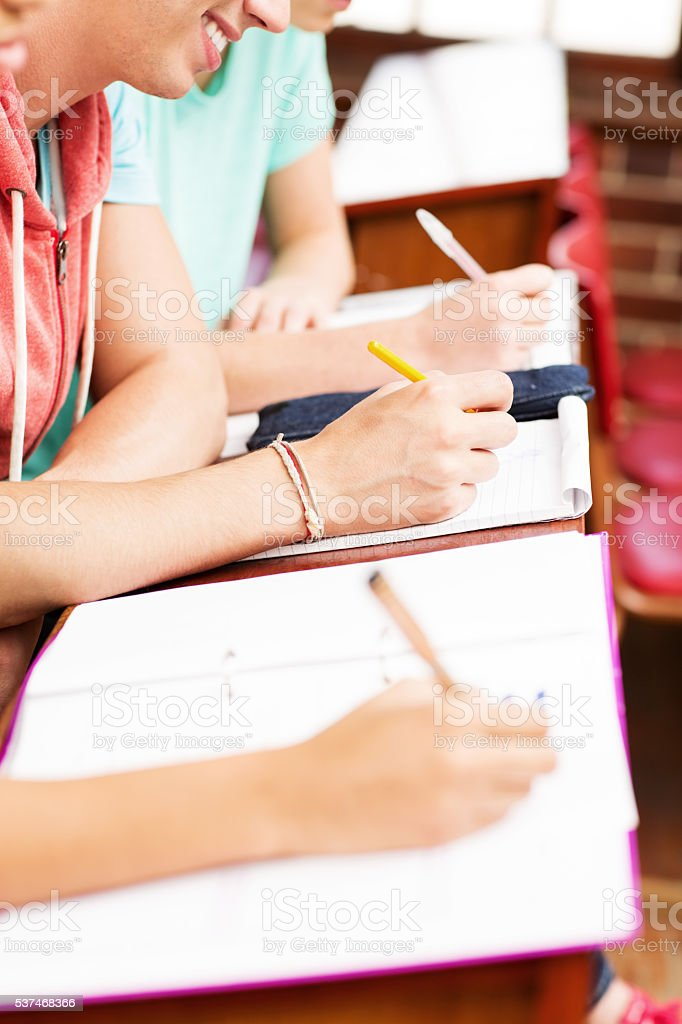 Students Writing In Book At Classroom Desk stock photo