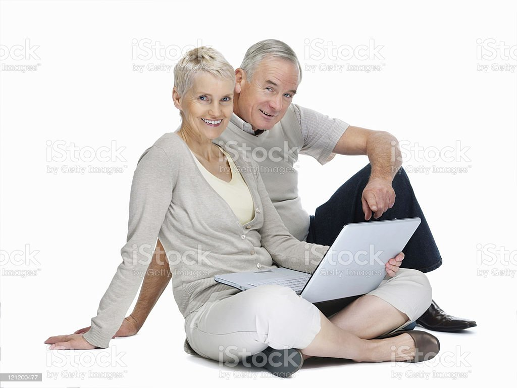 Studio image of old couple sitting with laptop on white royalty-free stock photo
