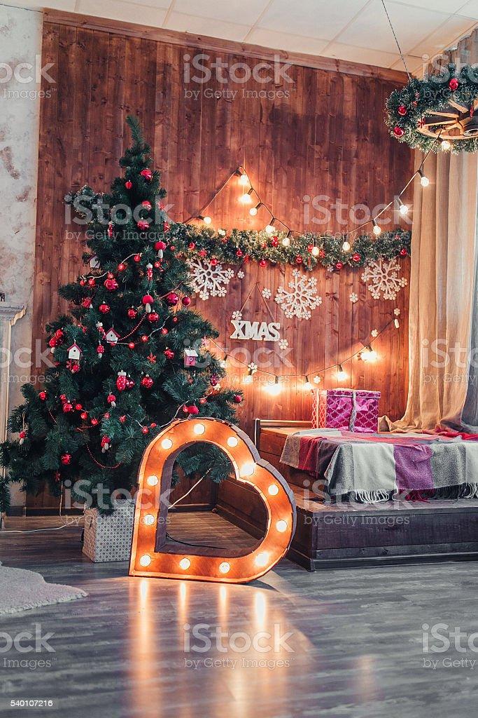 Studio interior with Christmas tree and illuminated heart stock photo