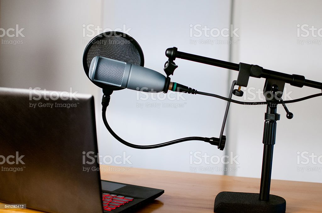 Studio microphone and a laptop sit on a desk stock photo