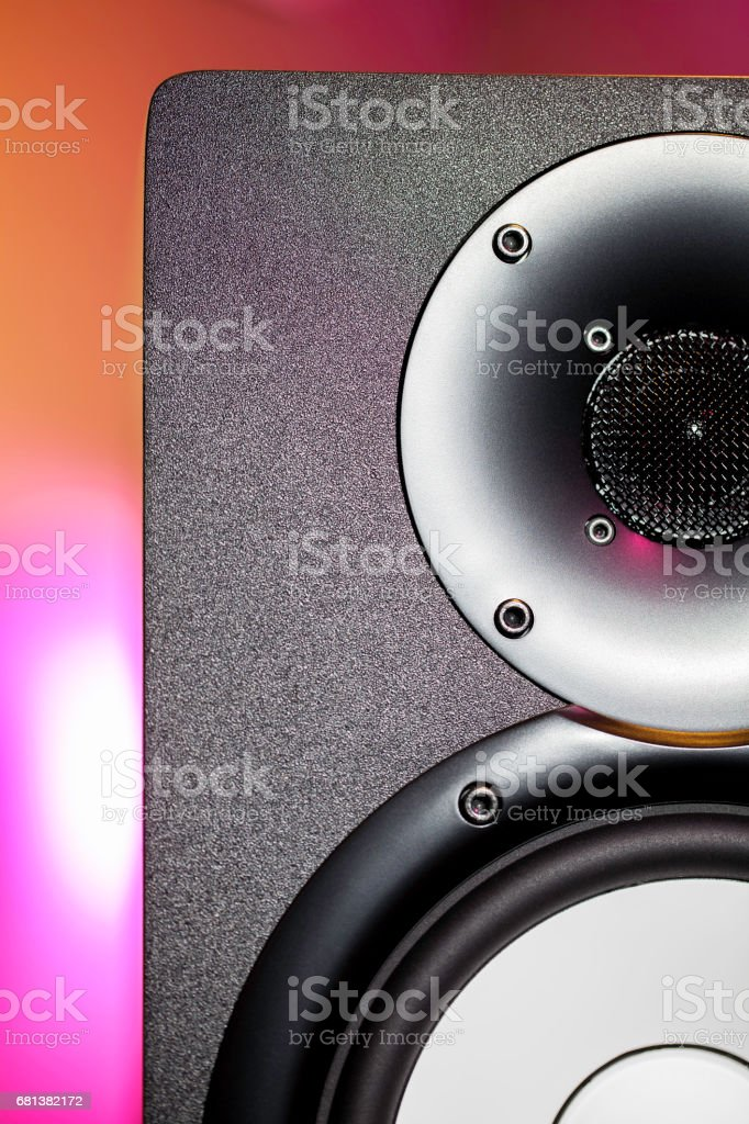 DJ studio monitor speaker with disco lighting background. Nightclub...