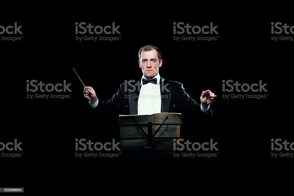 Studio photo of music conductor holding his baton stock photo