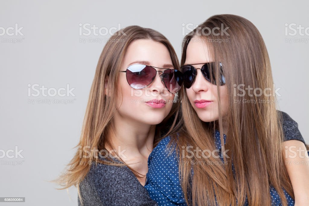 Studio portait of young twin sisters embracing stock photo