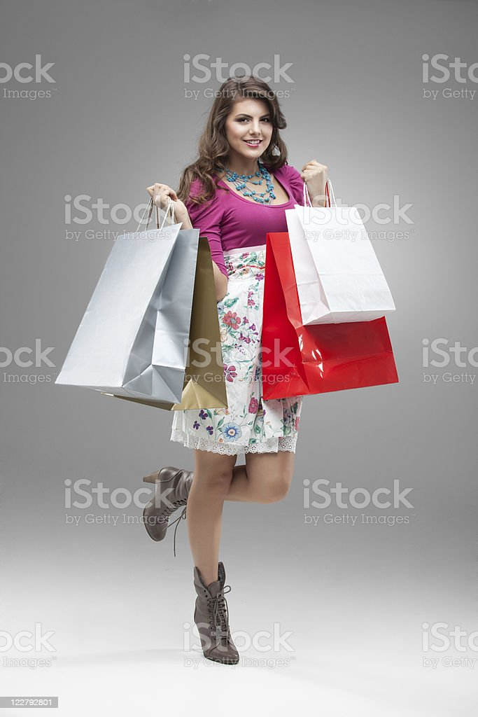 studio portrait of a young woman in colourful outfit holding stock photo