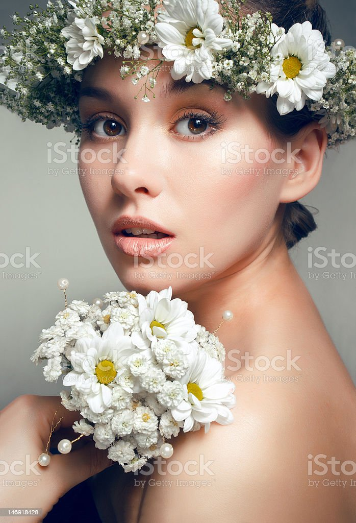 Studio portrait of beautiful woman with camomiles royalty-free stock photo
