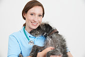 Studio Portrait Of Female Veterinary Surgeon Holding Lurcher Dog