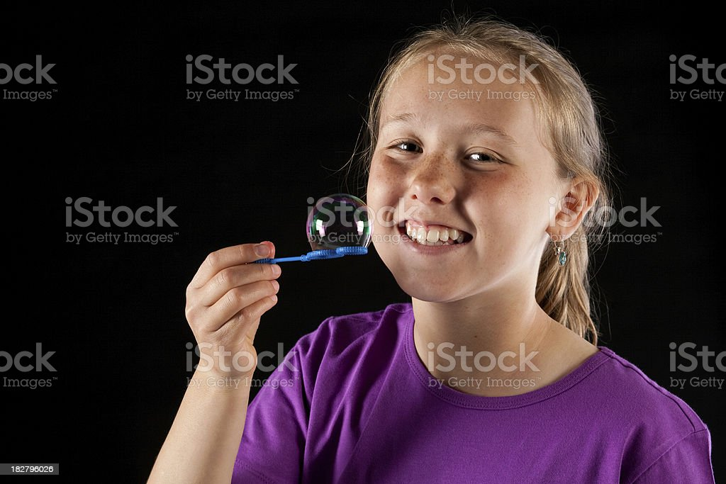 Studio portrait of girl holding soap bubble and smiling stock photo