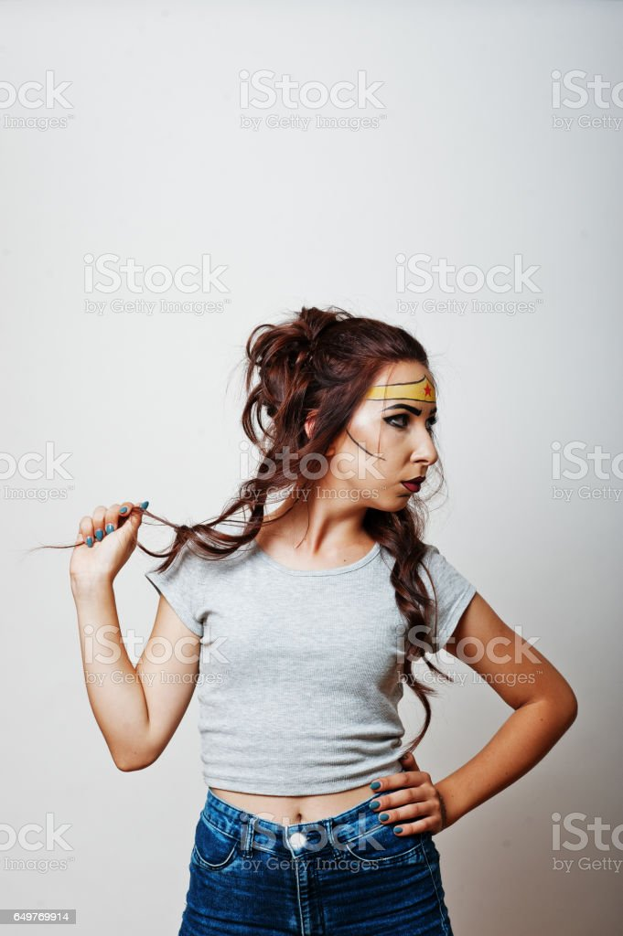 Studio portrait of girl with asian appearance and bright make up with red star on forehead stock photo