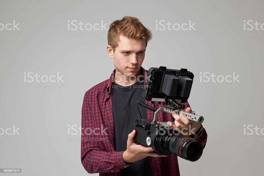 Studio Portrait Of Male Videographer With Film Camera stock photo