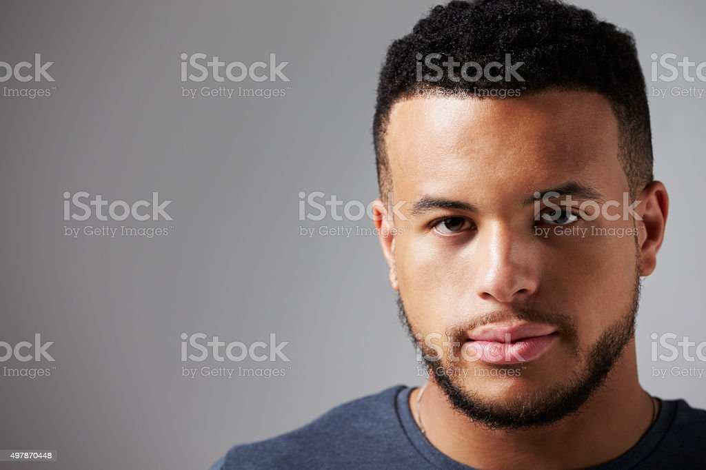 Studio Portrait Of Man Standing Against Grey Background stock photo