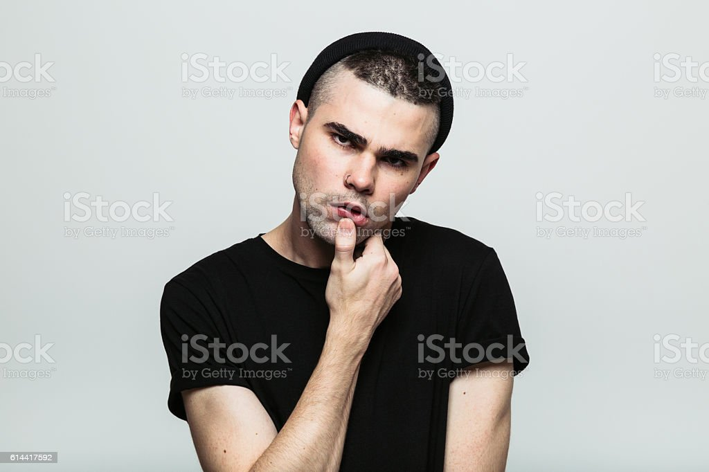 Studio portrait of man with hand on chin stock photo