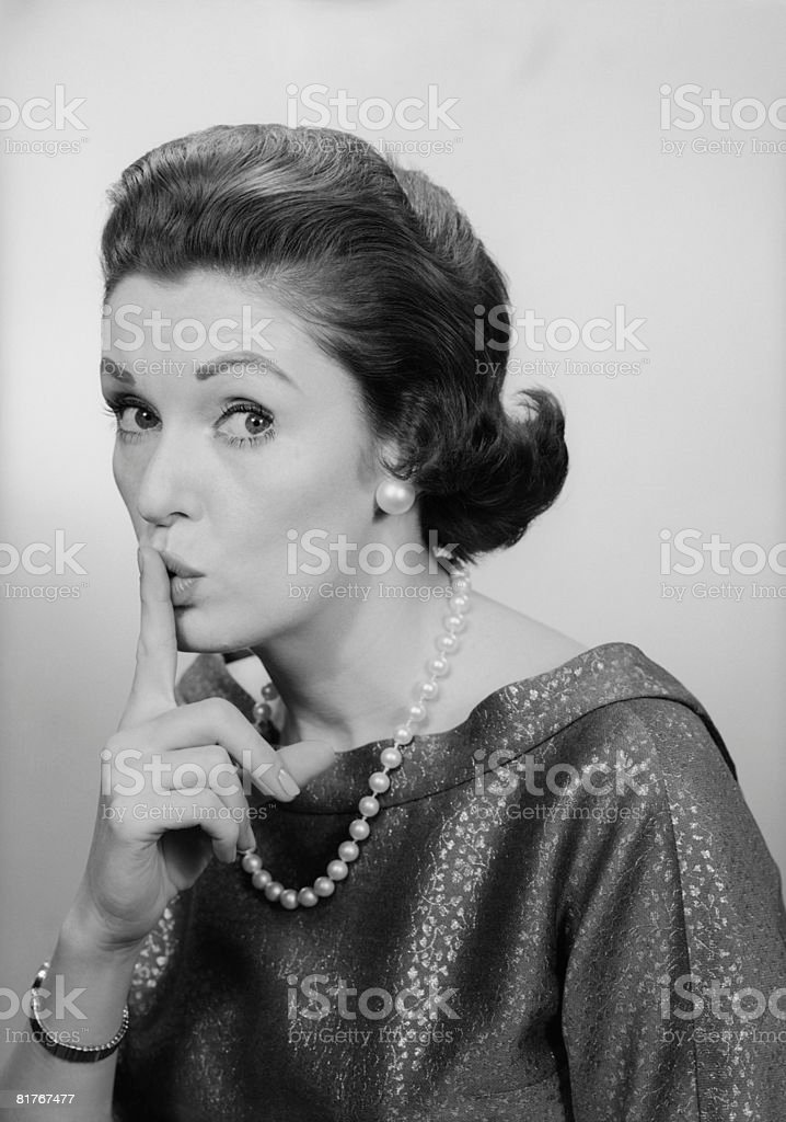 Studio portrait of mature woman holding finger to lips royalty-free stock photo
