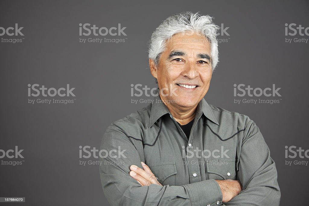 Studio portrait of smiling hispanic mature man with grey hair royalty-free stock photo