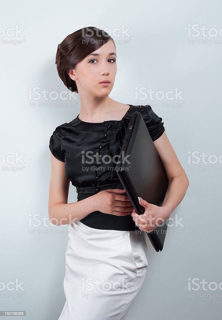 Studio portrait of young business woman holding laptop royalty-free stock photo