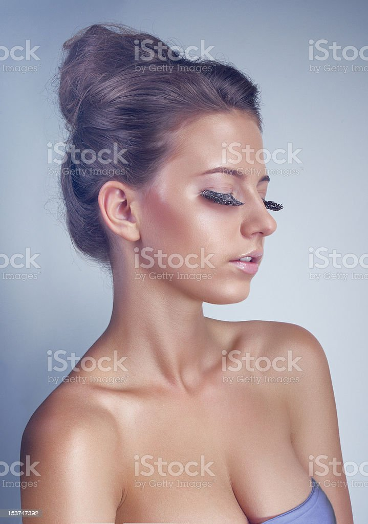 Studio portrait of young woman with long feather eyelashes royalty-free stock photo