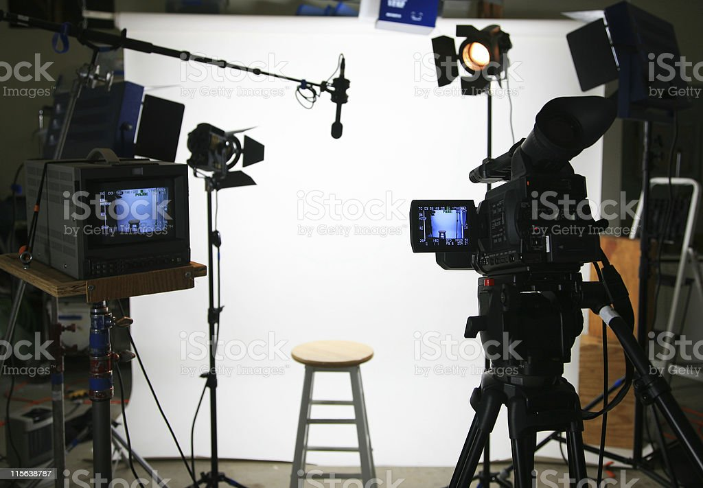 Studio interview setup in front of a white background with a stool...