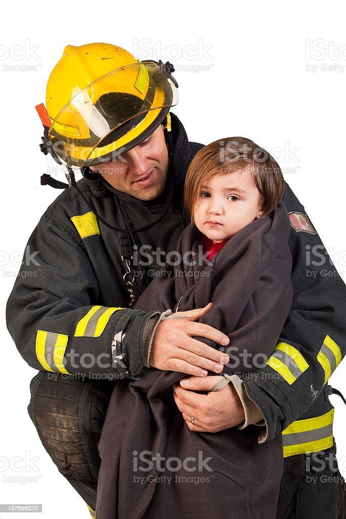 Studio shot of a fireman holding little girl in blanket. stock photo