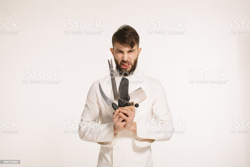 Studio shot of a happy bearded young chef holding sharp knives over white background. Chef with knife. Handsome angry serious cheef holding many sharp knives isolated against white background. stock photo