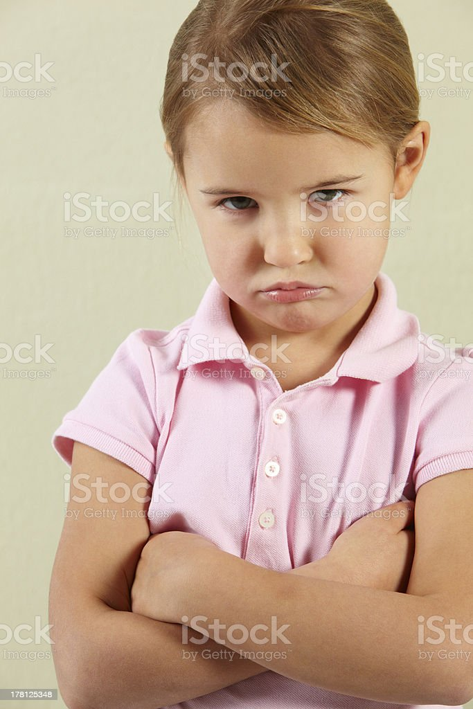 Studio Shot Of Angry Young Girl With Arms Crossed Looking At Camera