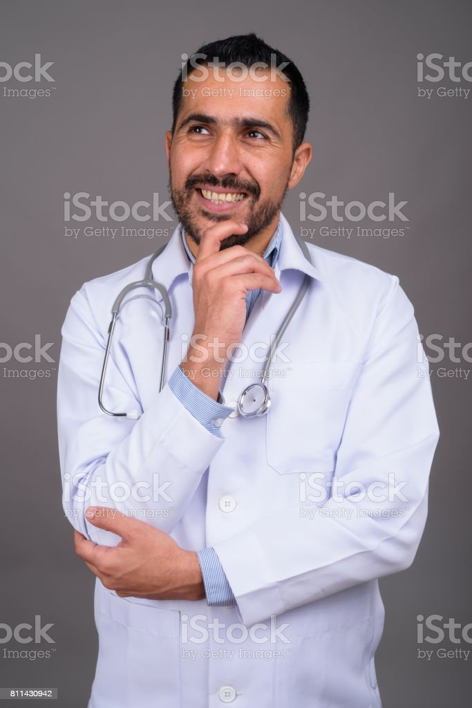 Studio shot of bearded Persian man doctor against gray background stock photo
