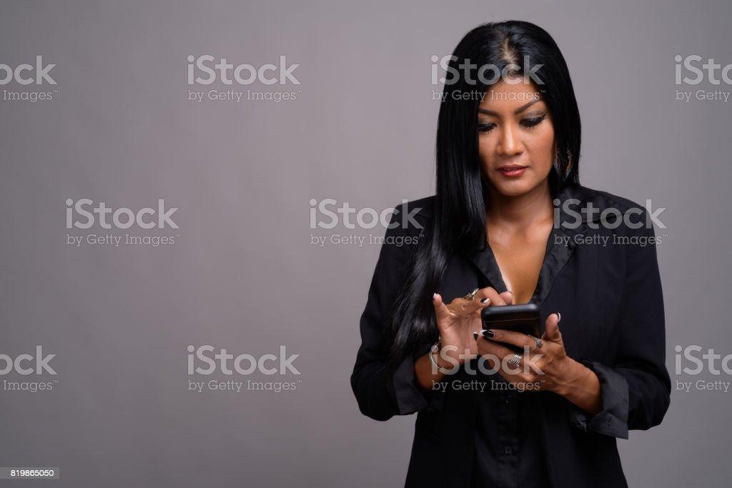 Studio shot of beautiful Asian businesswoman against gray background stock photo